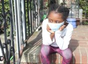 Young black girl wearing mask sitting on steps
