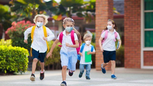 Kids in masks running through school yard