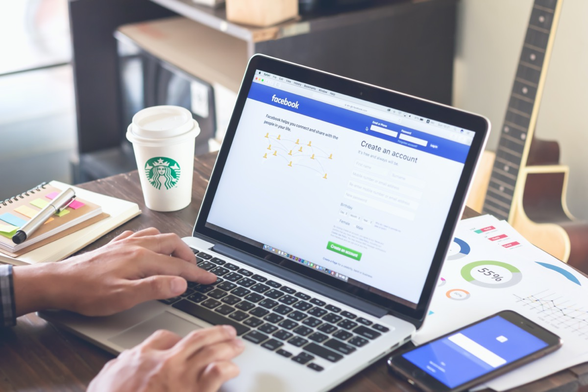 Person logging into Facebook on laptop at coffeeshop