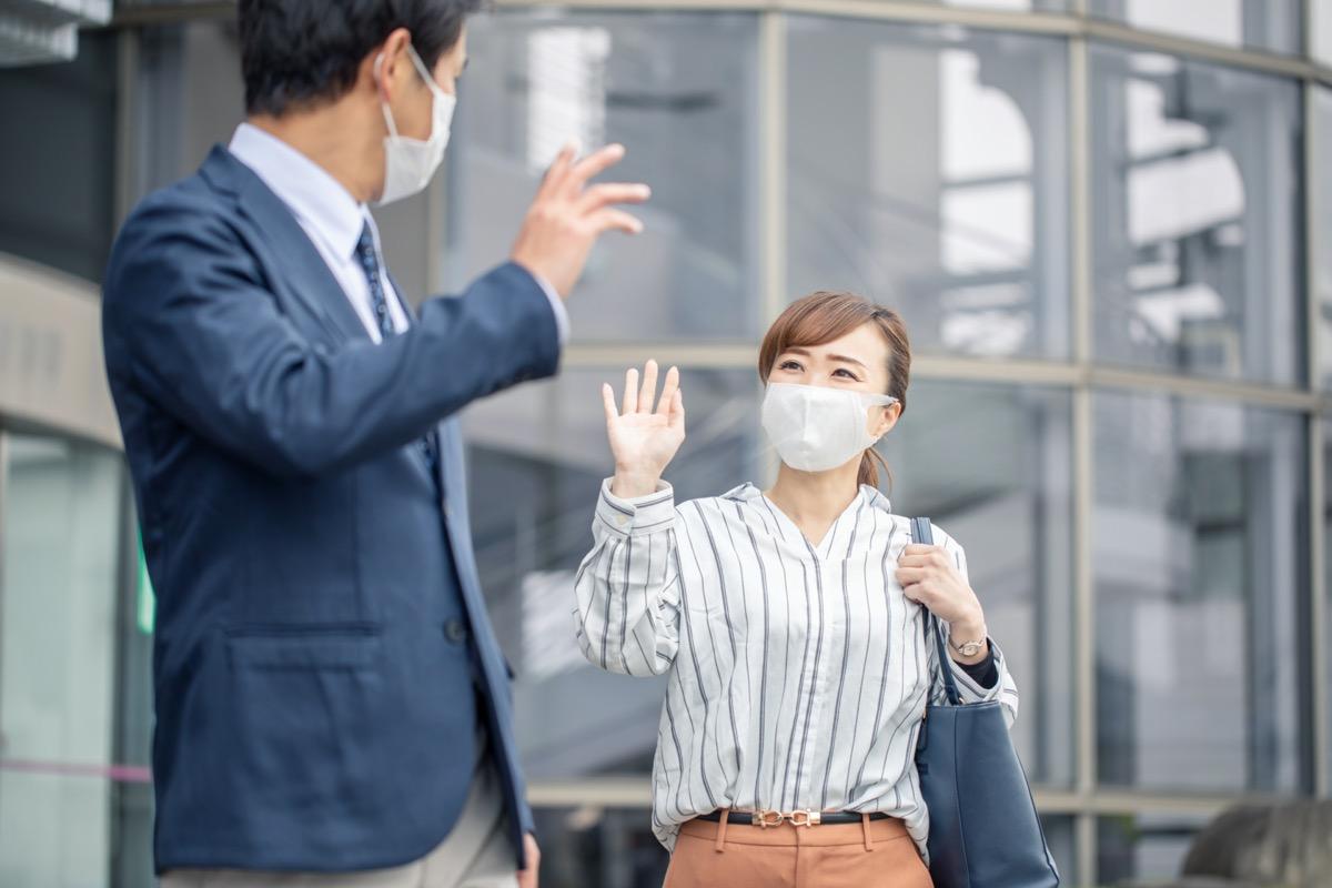 Asian woman and Asian man both waving and wearing masks