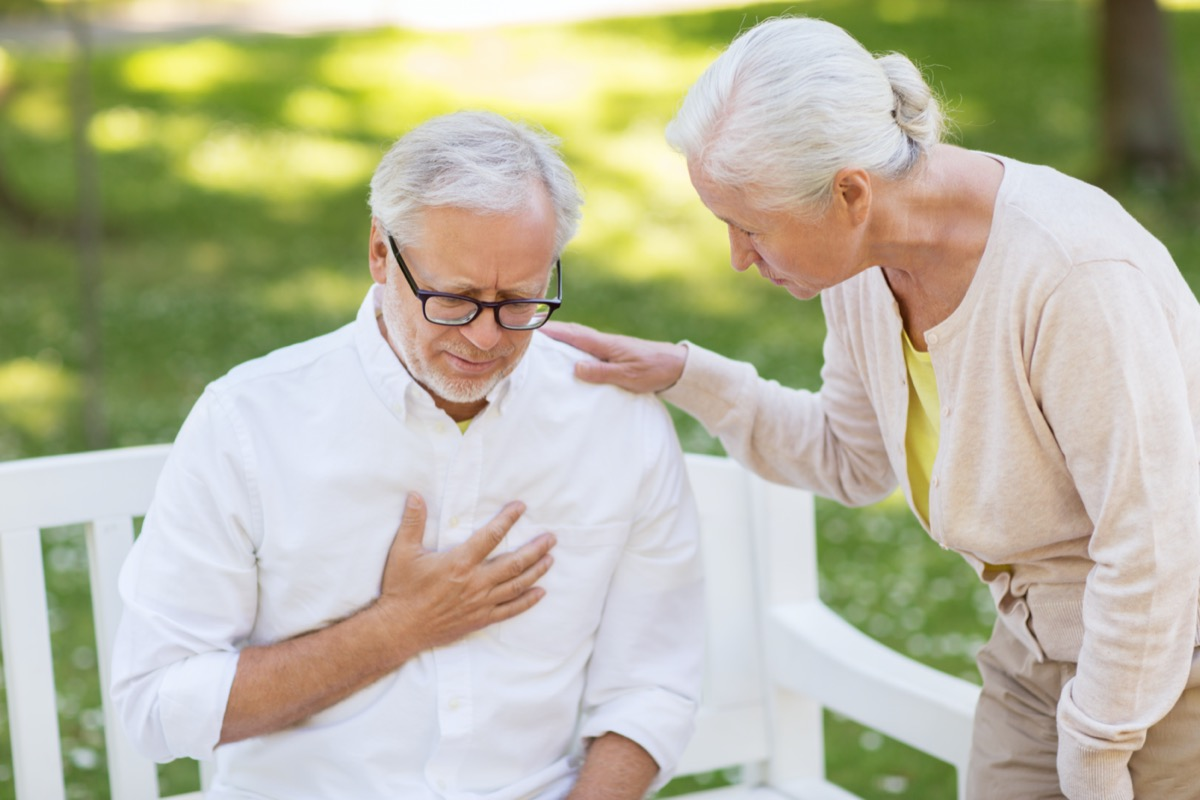 Senior man holding chest and woman checking on him
