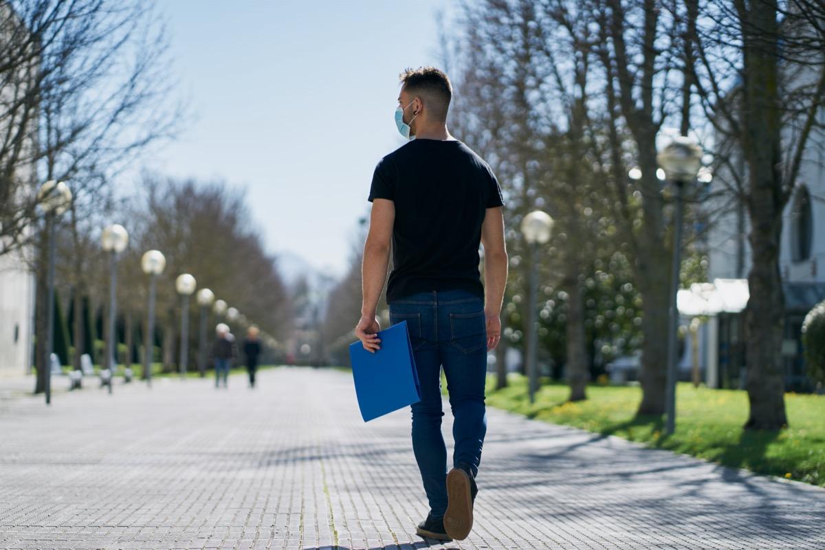 Man walking on sidewalk wearing mask