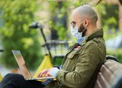 Man in park wearing white mask and using laptop