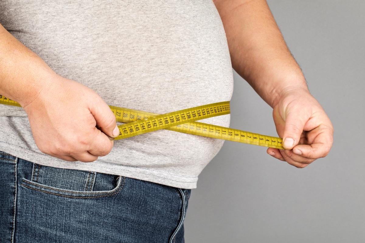Heavy man measuring his waist