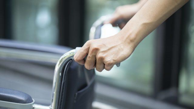 Hands pushing empty wheelchair