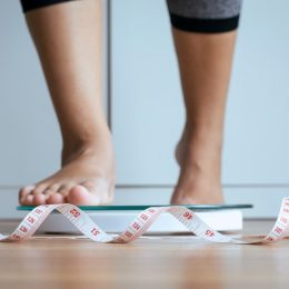 Woman stepping on scale with measurement tape