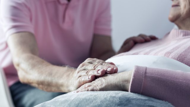 Man holding hand of dying woman