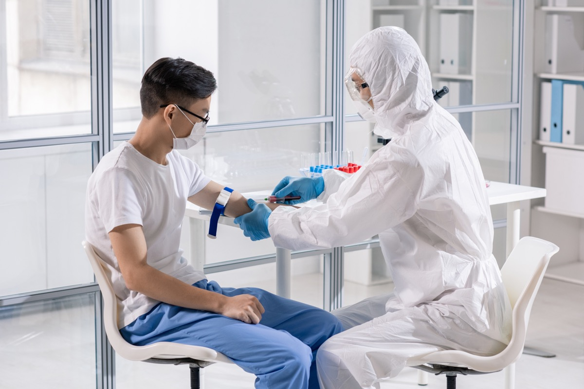 Young man in mask sitting in lab while doctor in protective coveralls taking his blood in syringe for analysis