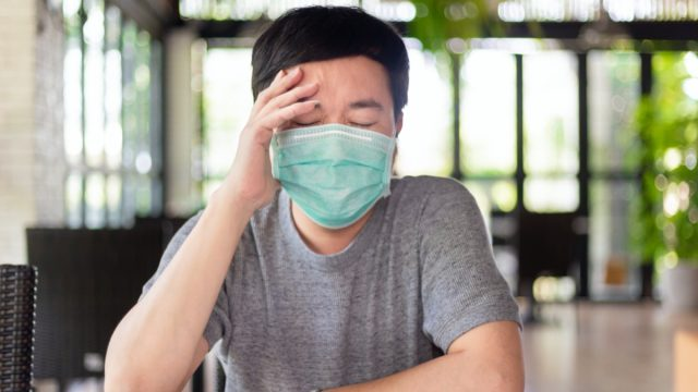 asian man wearing a mask has a headache