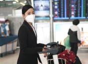 young asian woman wearing coronavirus mask in airport