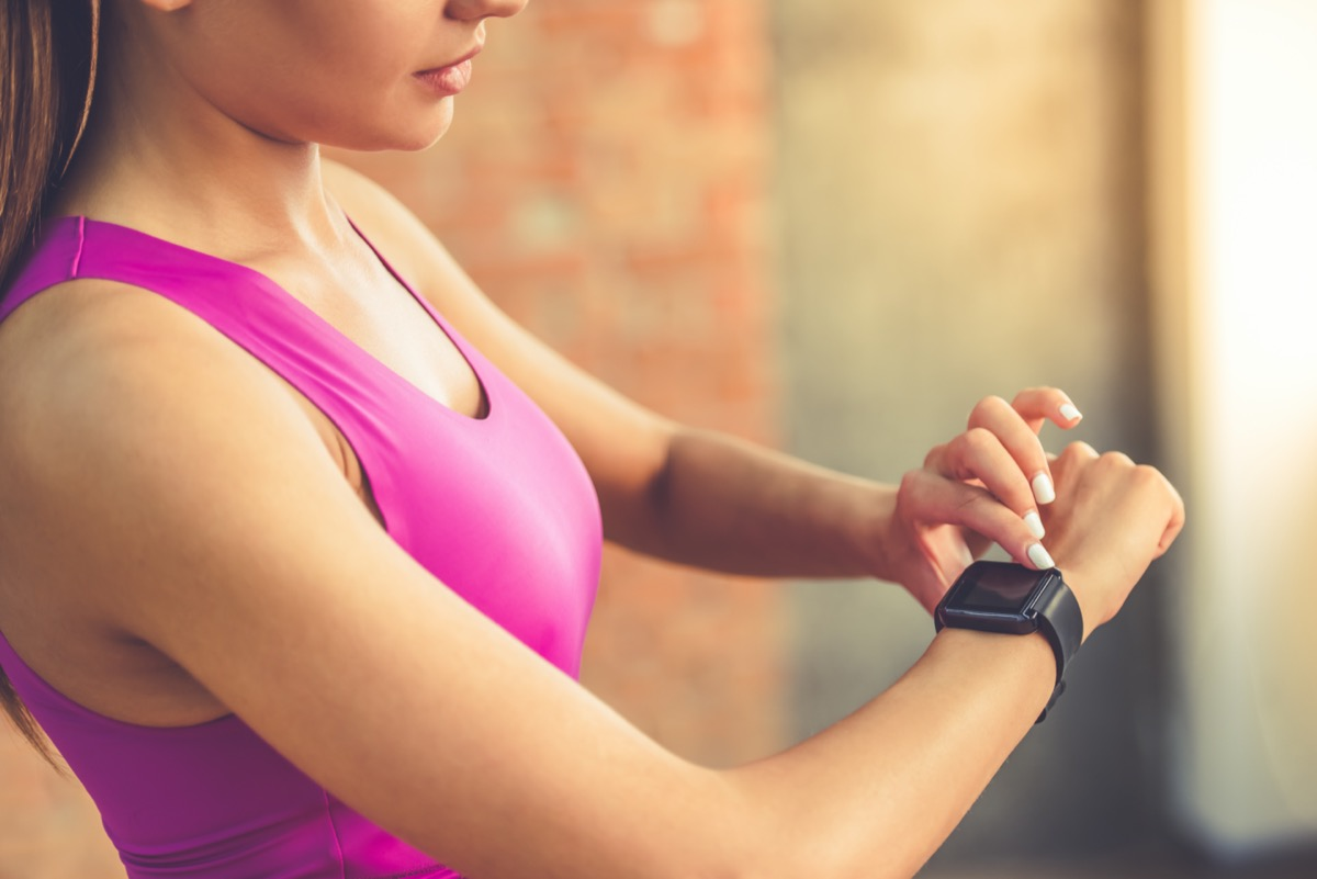 an athletic woman checks her fitbit