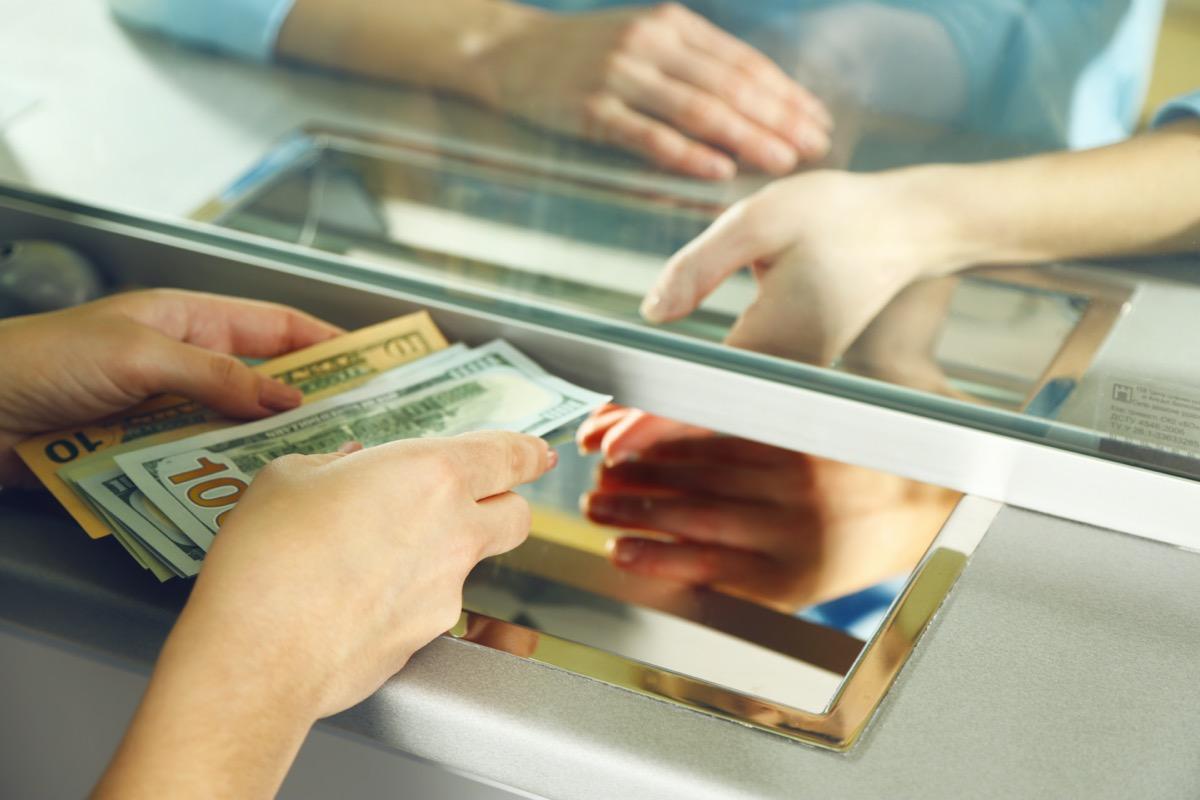 white hands passing cash under bank divider window