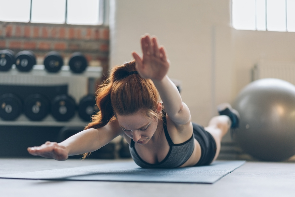 Young woman toning her abdominal muscles working out on a mat in a gym