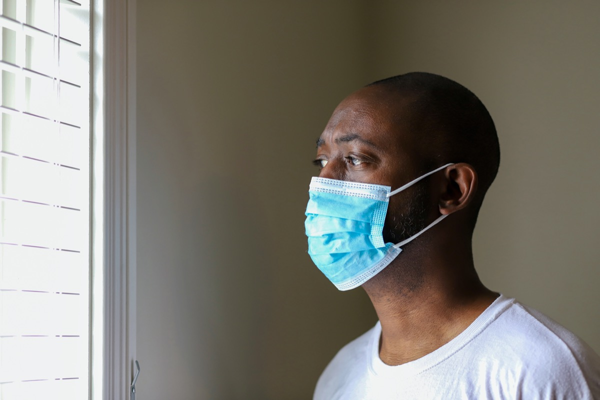 young black man looking out window wearing face mask