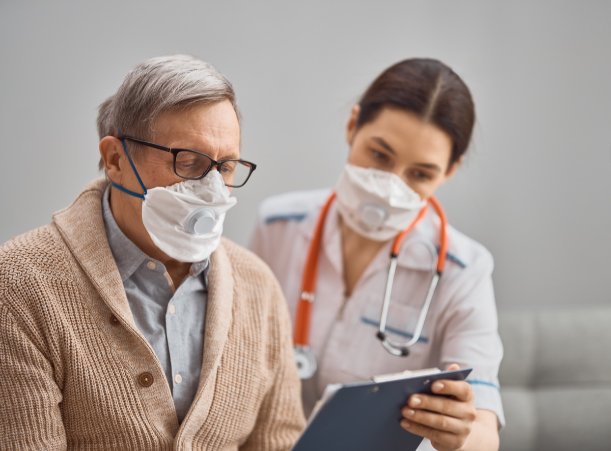Older patient wearing a mask with nurse