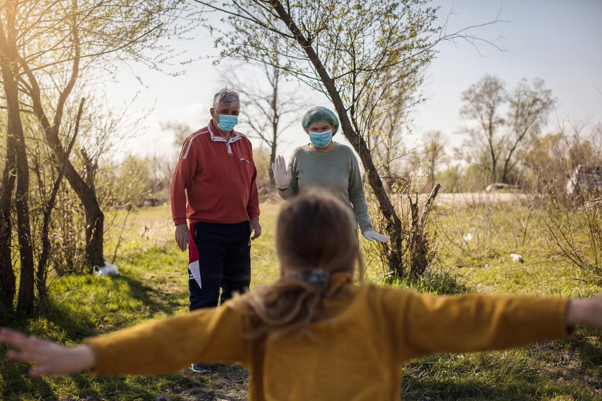 Granddaughter runs grandparents into a hug during the coronavirus pandemi
