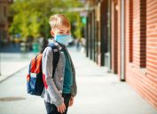Child wearing backpack and mask going to school