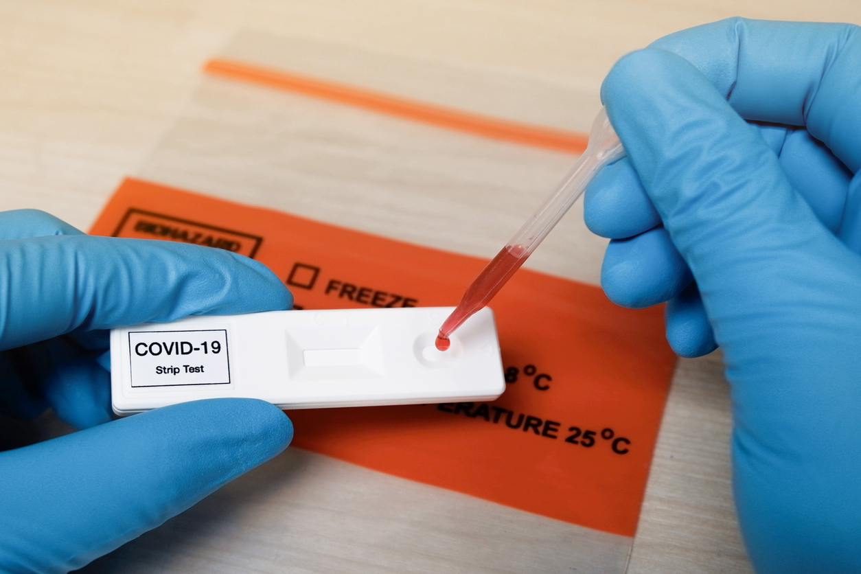 A close up of a technician wearing blue gloves placing a drop of blood on a COVID-19 antibody test strip