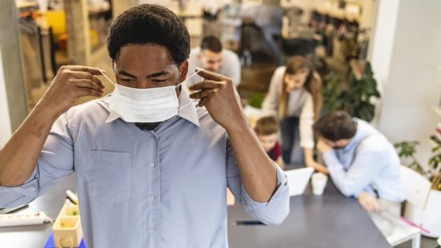 Black businessman in mask in working environment