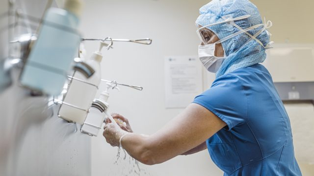 A female nurse washing her hands at a hospital sink