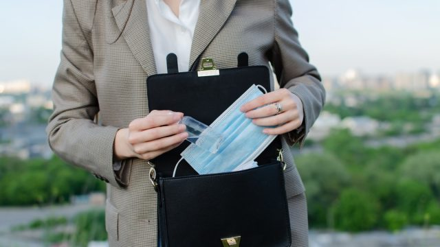 medical mask in a woman's bag, a handbag with protective equipment, in female hands closeup