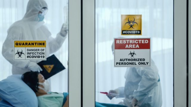 older woman in coronavirus isolation room in hospital