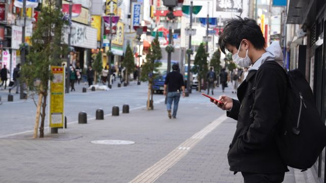 A Japanese man checking his phone while waiting in deserted Kabukicho district in downtown Tokyo