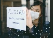 """An Asian woman wearing a face mask putting up a """"closed until further notice"""" sign"""