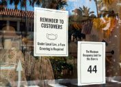 Two signs in a store window limiting occupancy to 44 and requiring a face mask.