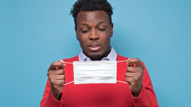 african american man in a red sweater looking cautiously at a protective face mask