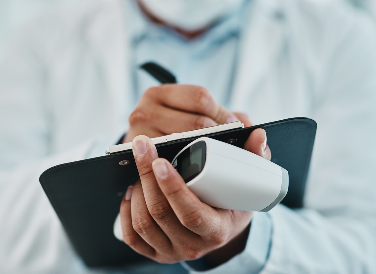 Cropped shot of a doctor holding an infrared thermometer and writing notes during an outbreak