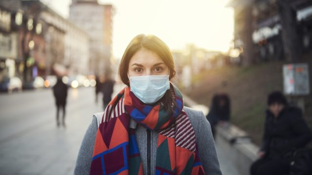 Portrait of young woman with protective face mask on the street, looking at camera