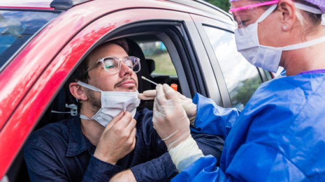 A white male wearing glasses has a nasal swab for a coronavirus test performed by a female doctor wearing protective gear