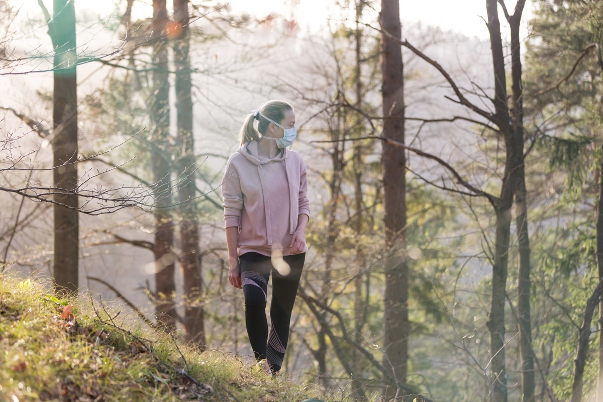 Portrait of sporty woman wearing a medical protection face mask while walking in the forest. Corona virus, or Covid-19, is spreading all over the world.