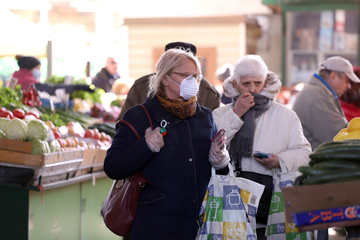 People, with face masks for protection from COVID-19, are shopping vegetables and fruits at marketplace in Sofia, Bulgaria – march 17, 2020.