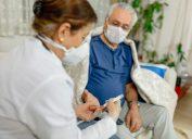 man gets blood sugar levels checked by nurse, both wear masks