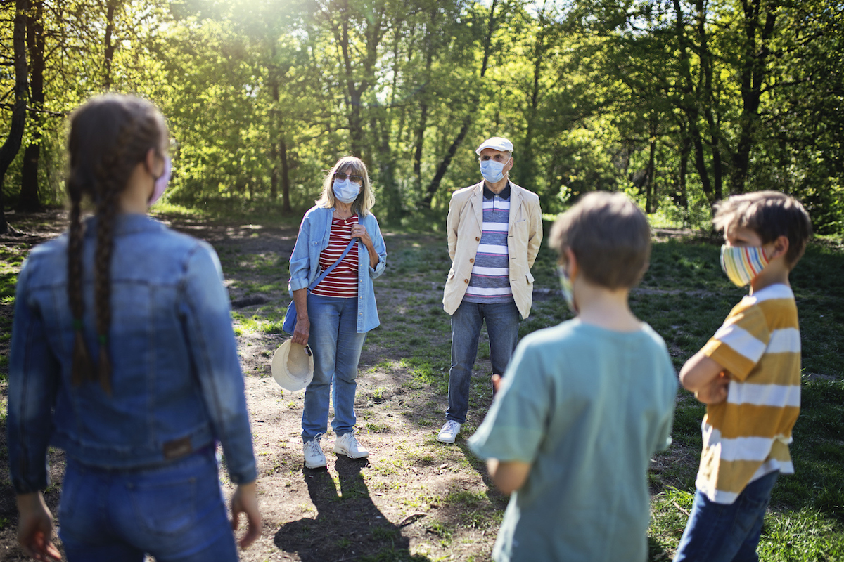 Grandparents and grandchildren meeting in the park with keeping distance and wearing masks.