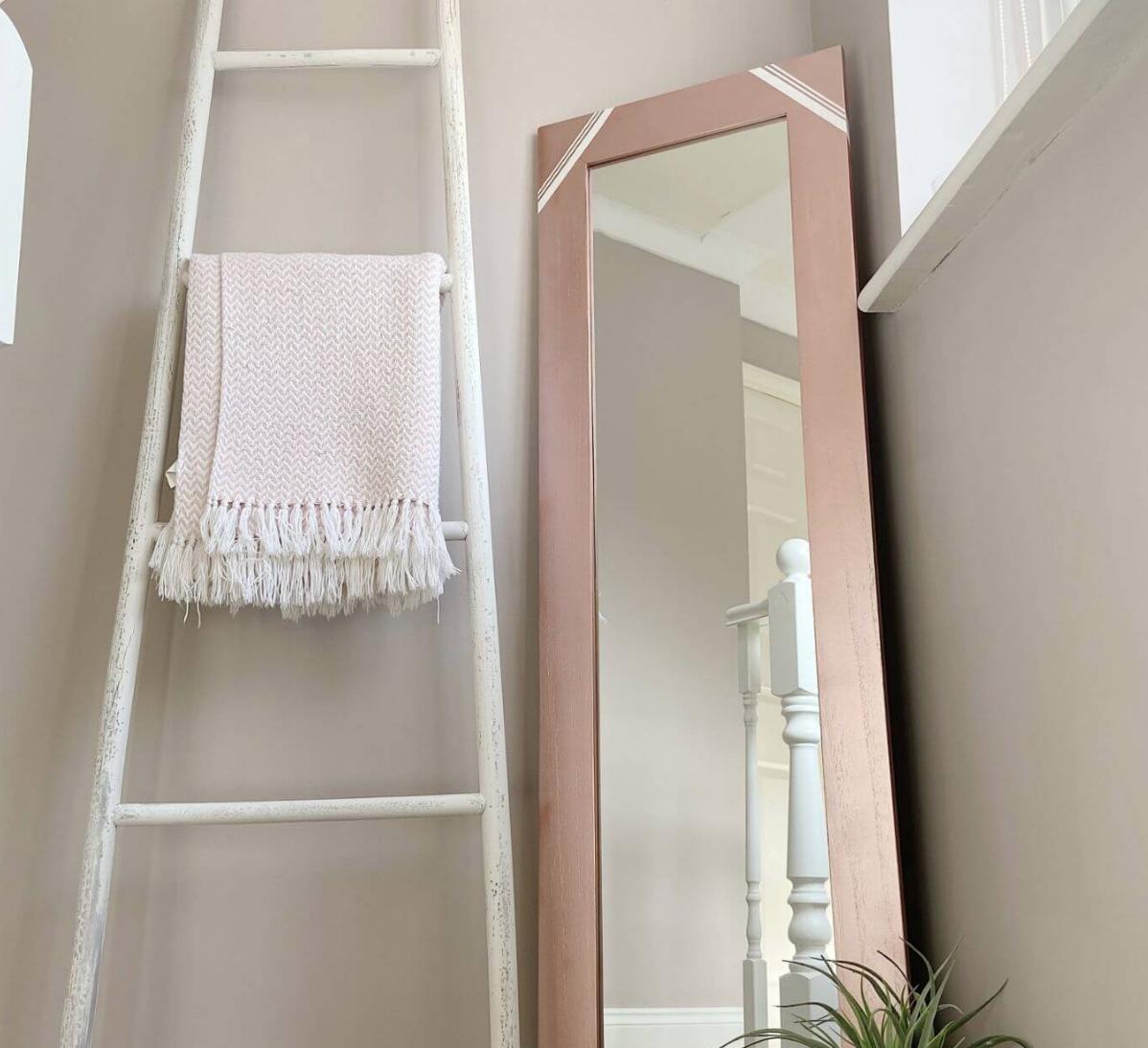 pink mirror next to blanket ladder