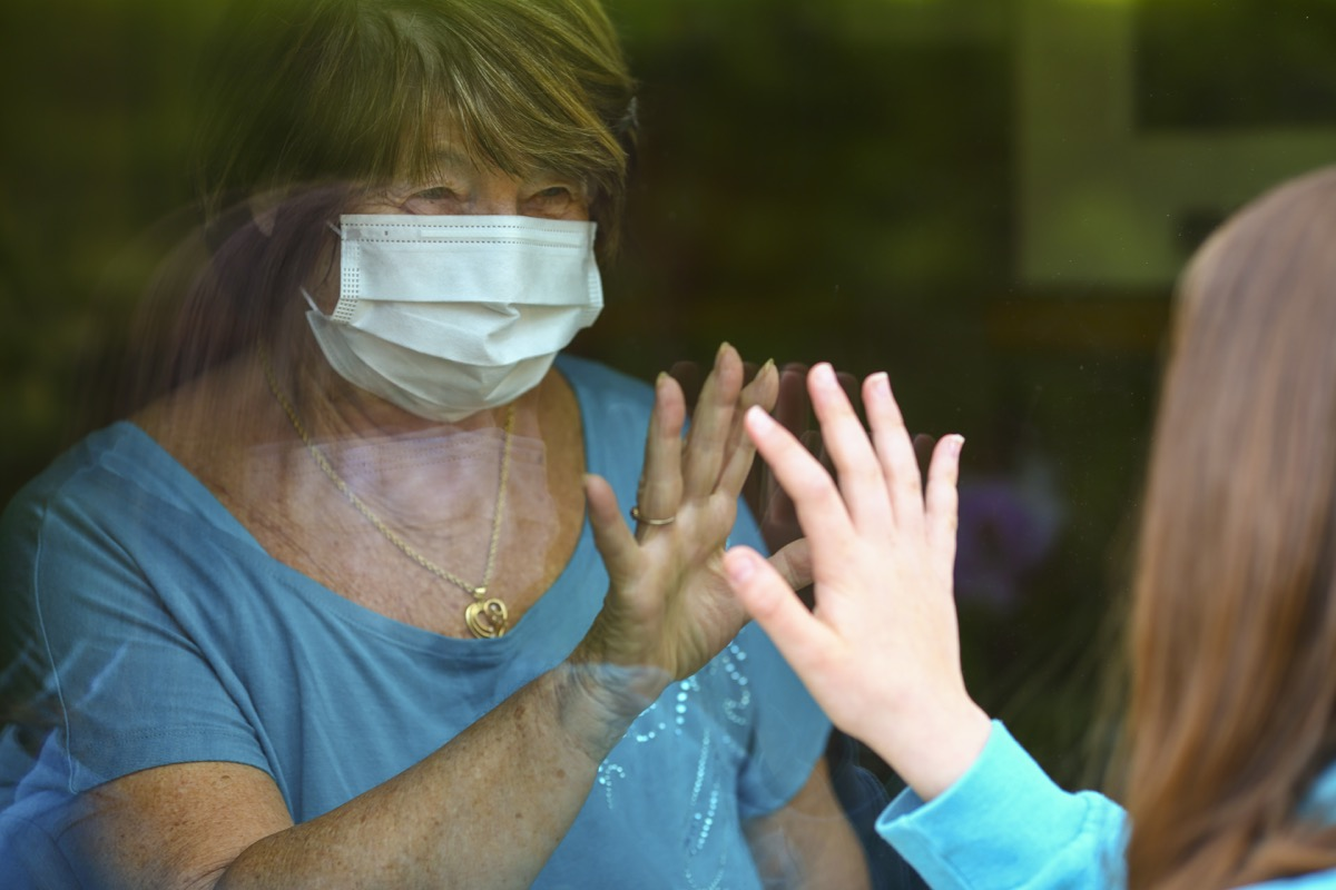 Grandmother and granddauther touch hands on window while on visit. Senior woman staying at home in time of quarantine for coronavirus or Covid-19. Lockdown visit of a senior adult.