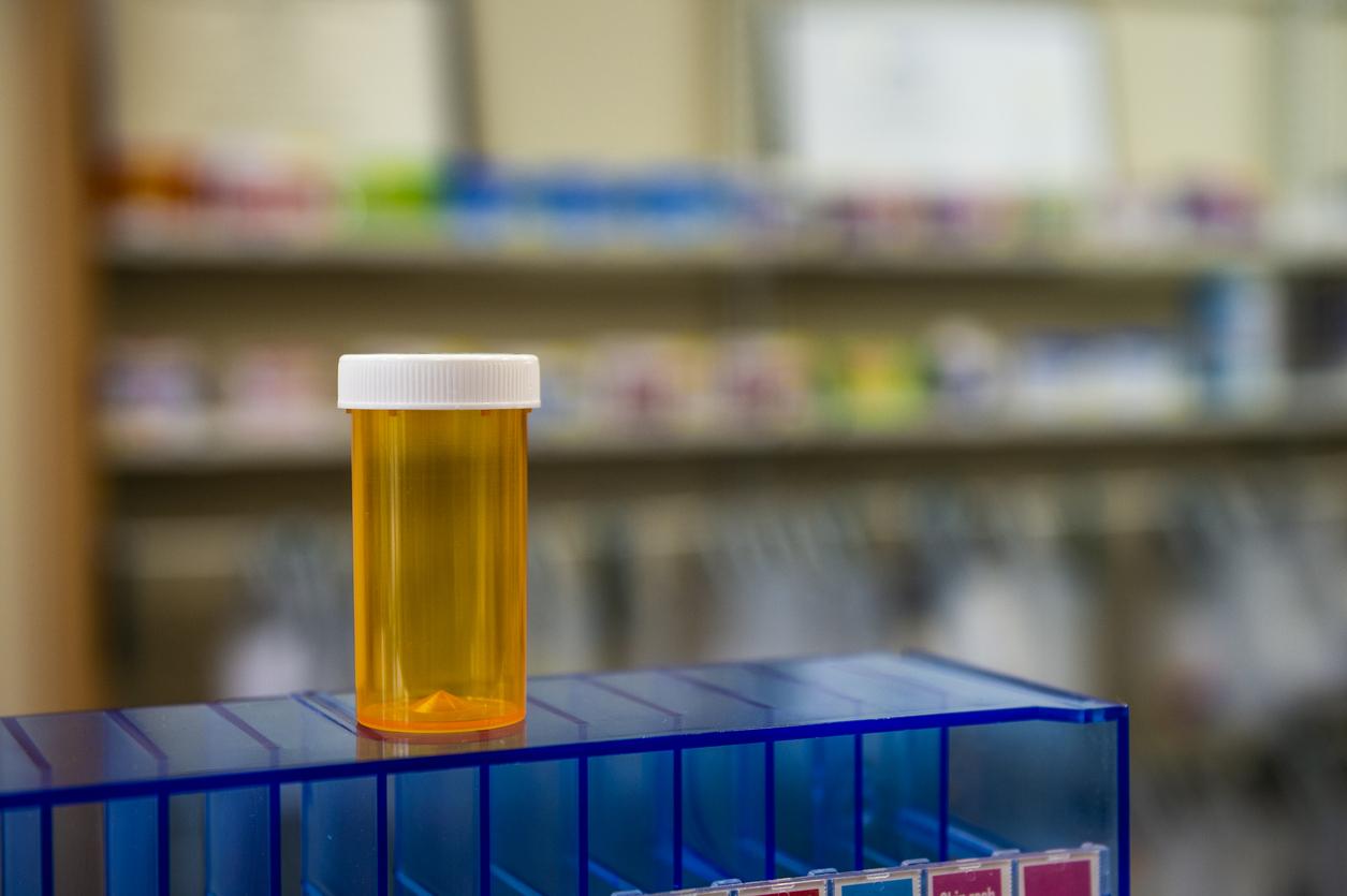 An empty prescription bottle standing on a blue case in a pharmacy