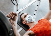 man in medical mask exercising with barbell in gym