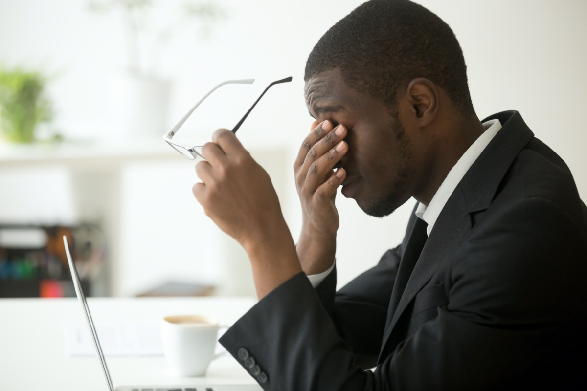 Young business man rubbing eyes at desk