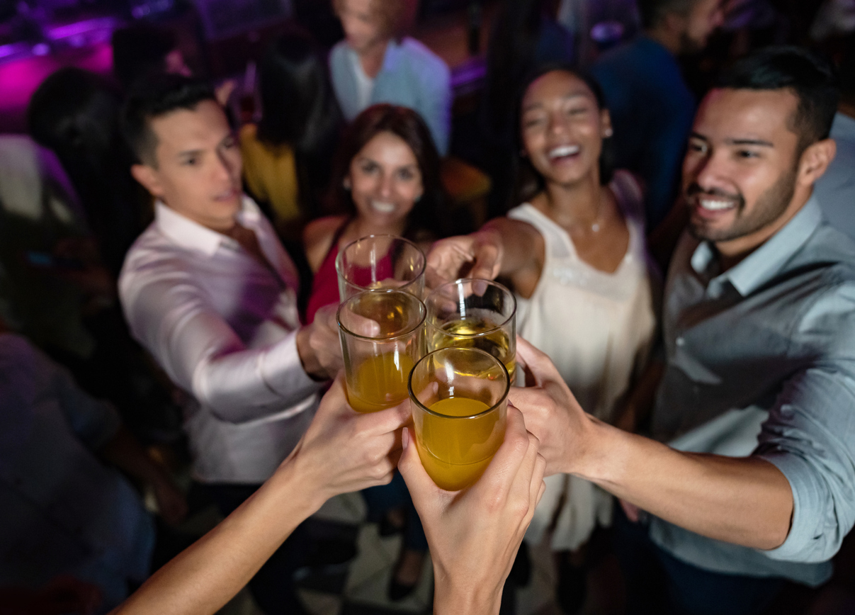 a group of multi ethnic friends makes a toast on the dance floor of a crowded nightclub