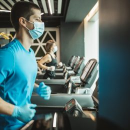 man and woman use treadmills at a gym with masks on