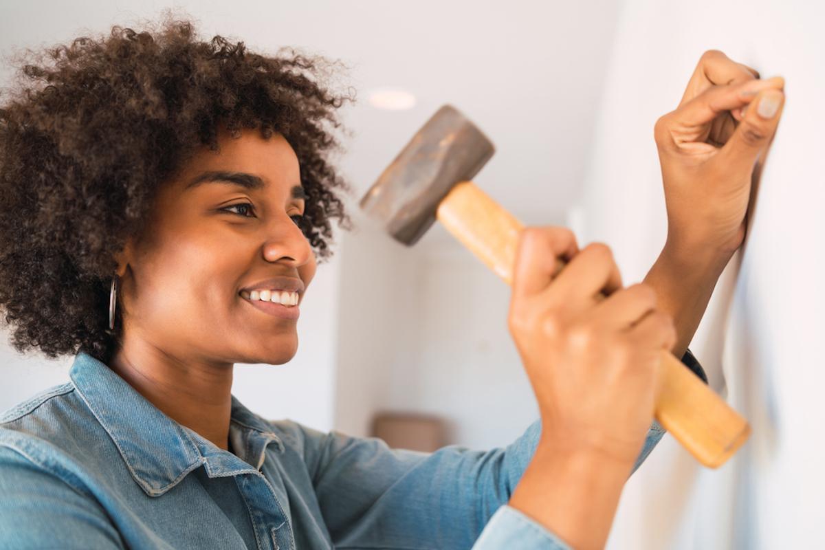young woman hammering nail into wall
