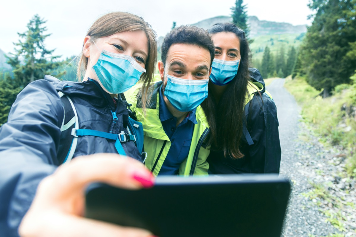 three friends take a selfie with masks on during a hike