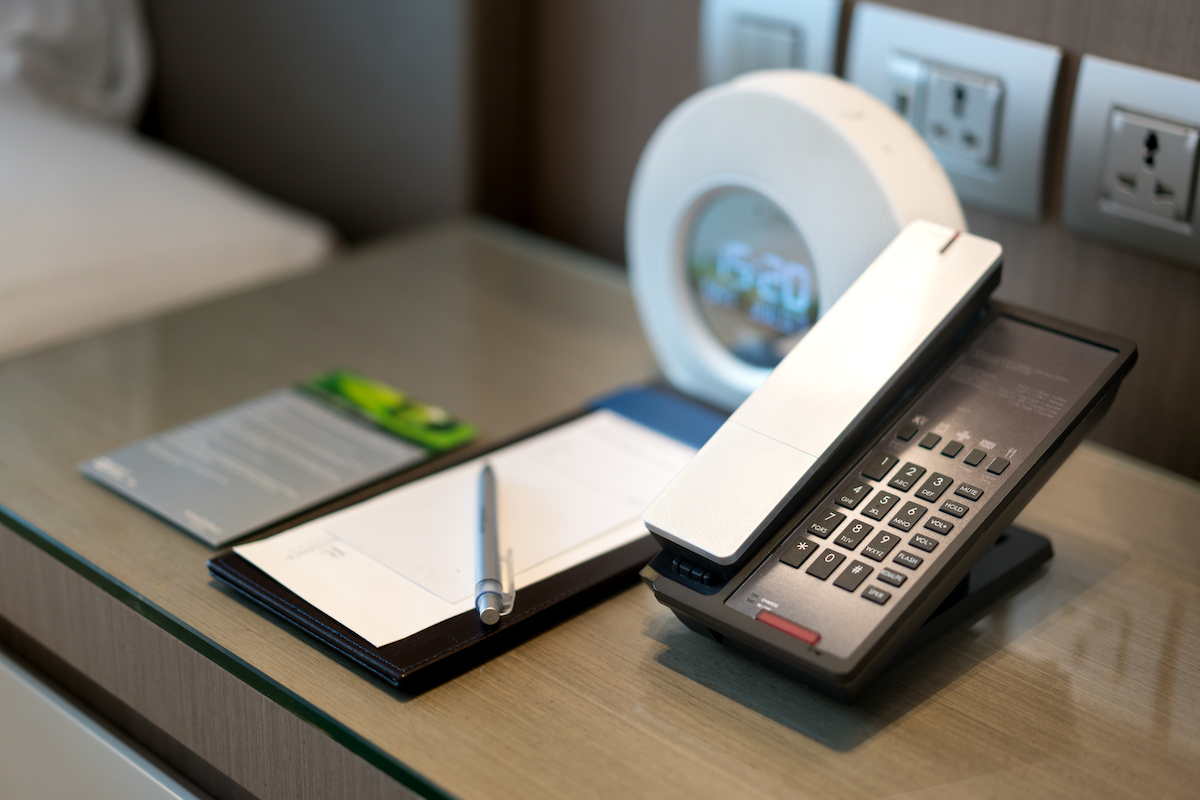 pen and paper and phone on desk in hotel