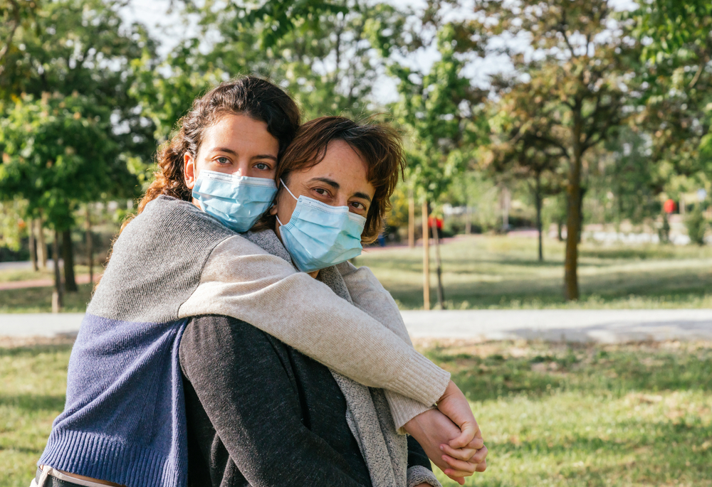 A daughter hugs her mother from behind in a park as both wear face masks