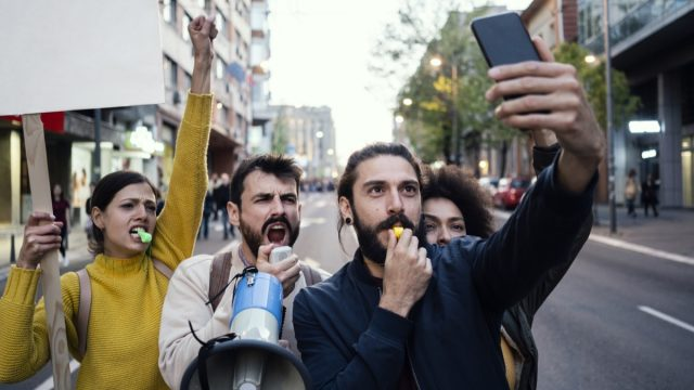 white male protester taking a selfie with three other protesters