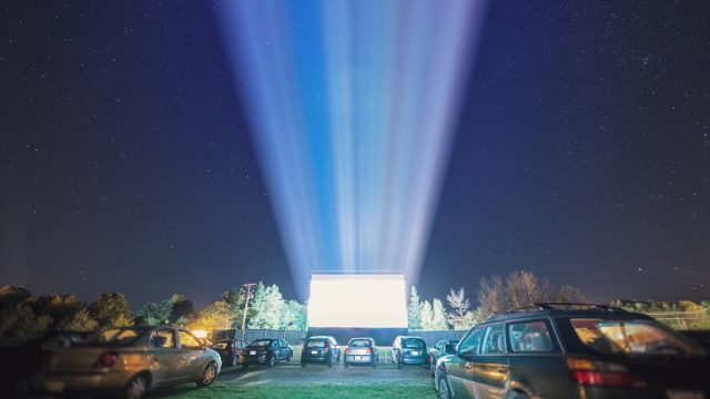 cars at a drive-in movie theater at night
